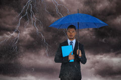 Composite image of portrait of serious businessman holding blue umbrella and file. Portrait of serious businessman holding blue umbrella and file  against stormy Stock Photo