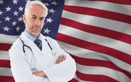 Composite image of portrait of a serious confident male doctor at medical office Royalty Free Stock Photos