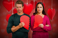 Composite image of portrait of serious couple holding cracked heart shape 3d. Portrait of serious couple holding cracked heart shape  against valentines heart Stock Photo