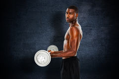 Composite image of portrait of a serious fit young man lifting barbell Royalty Free Stock Photography