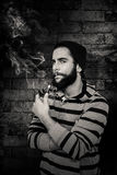 Composite image of portrait of serious hipster smoking pipe Royalty Free Stock Image
