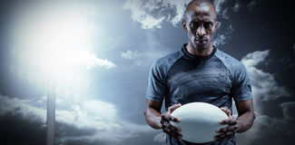 Composite image of portrait of serious sportsman holding rugby ball Royalty Free Stock Images