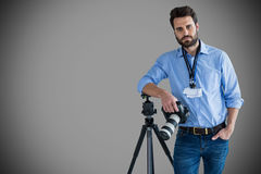Composite image of portrait of serious young photographer holding camera while leaning on tripod. Portrait of serious young photographer holding camera while Stock Photos
