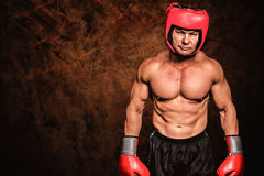 Composite image of portrait of shirtless man with boxing headgear and gloves Royalty Free Stock Photos