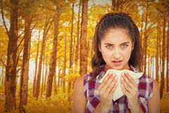 Composite image of portrait of sick woman sneezing in a tissue Royalty Free Stock Photos