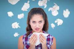 Composite image of portrait of sick woman sneezing in a tissue Royalty Free Stock Images