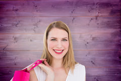 Composite image of portrait of a smiling blonde woman holding shopping bag Stock Photo