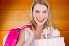 Composite image of portrait of a smiling blonde woman holding shopping bags Royalty Free Stock Images