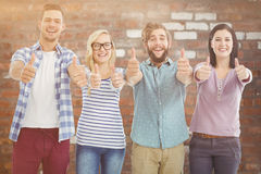 Composite image of portrait of smiling business people with thumbs up Stock Photo