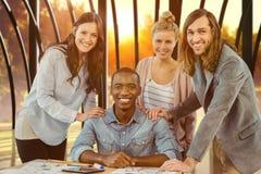 Composite image of portrait of smiling business team putting hands on man shoulder at desk Royalty Free Stock Photo