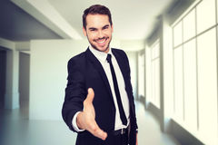 Composite image of portrait of smiling businessman offering handshake. Portrait of smiling businessman offering handshake against white room with screen Stock Images