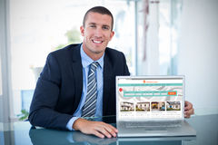 Composite image of portrait of smiling businessman showing laptop. Portrait of smiling businessman showing laptop against composite image of property web site Royalty Free Stock Images