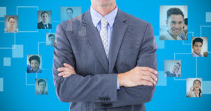 Composite image of portrait of smiling businessman standing hands folded Stock Photo