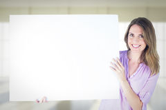 Composite image of portrait of smiling businesswoman holding blank billboard Royalty Free Stock Image