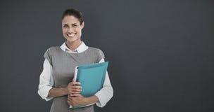 Composite image of portrait of smiling businesswoman holding file folder Stock Photo