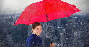 Composite image of portrait of smiling businesswoman holding red umbrella Royalty Free Stock Image