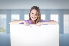 Composite image of portrait of smiling businesswoman pointing at blank billboard Stock Photos
