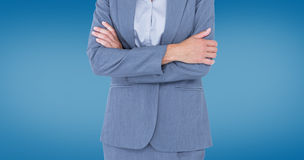 Composite image of portrait of smiling businesswoman standing arms crossed. Portrait of smiling businesswoman standing arms crossed against royal blue Royalty Free Stock Photos