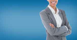 Composite image of portrait of smiling businesswoman standing arms crossed. Portrait of smiling businesswoman standing arms crossed against royal blue Stock Image