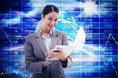 Composite image of portrait of a smiling businesswoman using a tablet computer Royalty Free Stock Photography