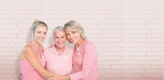 Composite image of portrait of smiling daughters with mother supporting breast cancer awareness Stock Photography