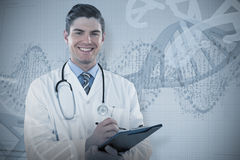 Composite image of portrait smiling doctor writing on clipboard. Portrait smiling doctor writing on clipboard against panoramic view of red dna pattern on screen Stock Photography