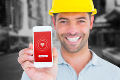 Composite image of portrait of smiling handyman showing smart phone. Portrait of smiling handyman showing smart phone against blurry new york street stock images