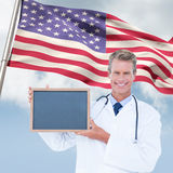 Composite image of portrait of smiling male doctor holding blank slate. Portrait of smiling male doctor holding blank slate against composite image of low angle Stock Image