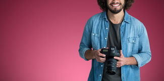 Composite image of portrait of smiling male photographer with camera. Portrait of smiling male photographer with camera  against red and white background Stock Photos