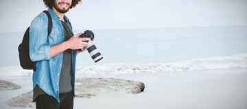 Composite image of portrait of smiling male photographer holding camera. Portrait of smiling male photographer holding camera  against beach Royalty Free Stock Photo
