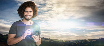 Composite image of portrait of smiling male photographer holding camera. Portrait of smiling male photographer holding camera against cloudy sky landscape Royalty Free Stock Photos