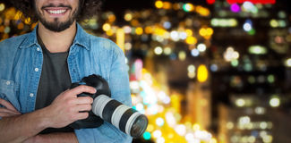 Composite image of portrait of smiling male photographer holding digital camera Stock Image