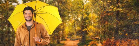 Composite image of portrait of smiling man holding yellow umbrella. Portrait of smiling man holding yellow umbrella against scenic view of walkway along lush Royalty Free Stock Image