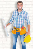 Composite image of portrait of smiling manual worker holding spirit level Royalty Free Stock Photo