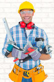 Composite image of portrait of smiling manual worker holding various tools Royalty Free Stock Images