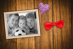 Composite image of portrait of smiling son, father and grandfather on floor. Portrait of smiling son, father and grandfather on floor against wooden table Royalty Free Stock Photos