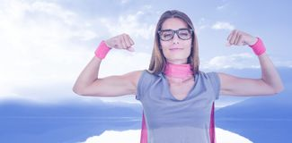 Composite image of portrait of smiling woman in superhero costume while flexing muscles Royalty Free Stock Photos
