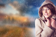 Composite image of portrait of smiling woman wearing winter coat Stock Photography