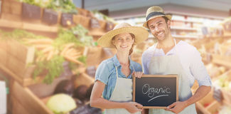 Composite image of portrait of smiling young couple holding writing slate together with organic text stock photo