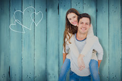 Composite image of portrait of smiling young couple piggybacking. Portrait of smiling young couple piggybacking against wooden planks Royalty Free Stock Image