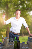 Composite image of portrait of smiling young man holding red wine glass by barrels Royalty Free Stock Image