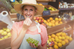 Composite image of portrait of smiling young woman eating grapes Royalty Free Stock Photography