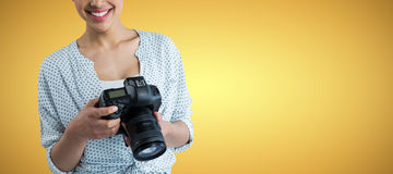 Composite image of portrait of smiling young woman holding digital camera. Portrait of smiling young woman holding digital camera against yellow vignette stock image