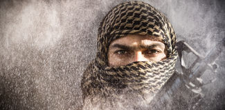 Composite image of portrait of soldier with covered face holding rifle. Portrait of soldier with covered face holding rifle against black Stock Photography