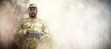 Composite image of portrait of soldier holding american flag royalty free stock photo