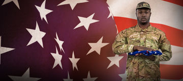 Composite image of portrait of soldier holding american flag Stock Images
