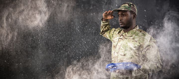 Composite image of portrait of soldier holding american flag and saluting Stock Photo