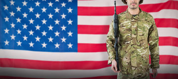 Composite image of portrait of soldier with rifle. Portrait of soldier with rifle against rippled us flag Royalty Free Stock Photos