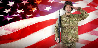 Composite image of portrait of soldier with rifle saluting Royalty Free Stock Photo