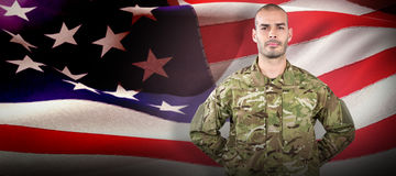 Composite image of portrait of soldier standing with hand behind back royalty free stock photos